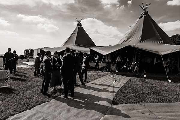 Guests mingling outside a stunning tipi structure