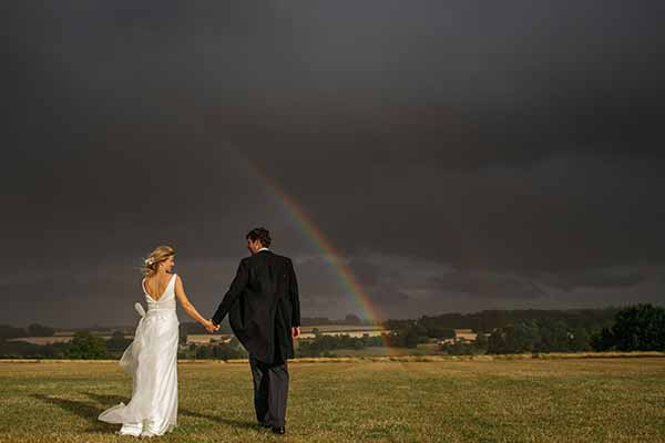 Bride and Groom walking in to a beautiful rainbow
