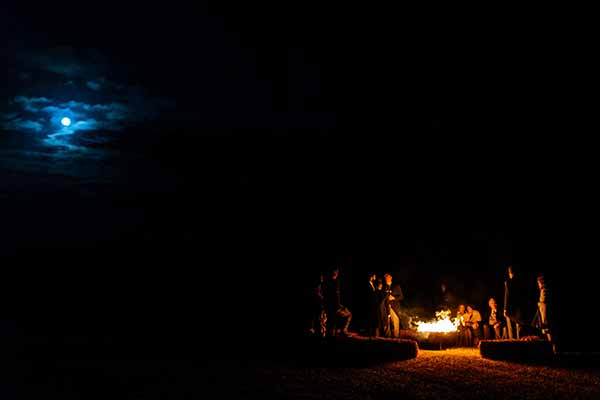 Wedding party enjoying the fire under the moon