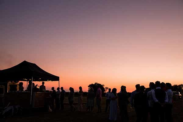 Guests waiting for pizza in a stunning sunset over the Cotswold Field of Dreams