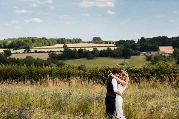 Bride and groom taking some time out to be together in the wild flower walkway on the Cotswold Field of Dreams
