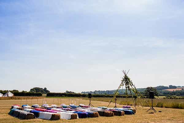 Ceremony being set up with straw bales, rugs and a bamboo tipi temple